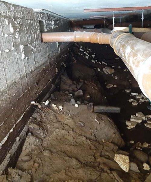 1970-luvulla rakennetun kerrostalon maanvaraisen laatan alla tyhjää tilaa, hulevesiä ja rakennusaikaista jätettä.